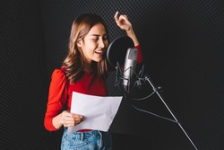 Pretty Asian female singer recording songs by using a studio microphone and pop shield on mic with passion in music recording studio. Performance and show in the music business. Image with copy space.