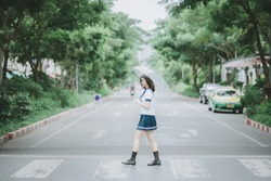 pretty asian girl in Japanese student uniform with short dark hair holding an umbrella and walking across the street in the middle of somewhere with a lot of trees along the street