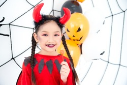 Pretty asian girl in red devil costume with horn sitting in room decorated for Halloween festival.