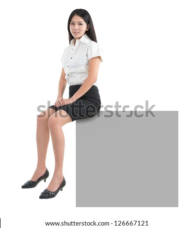 Pretty Asian girl sitting on big blank billboard poster sign with copy space. Smiling Asian Chinese young woman model. Isolated on white background