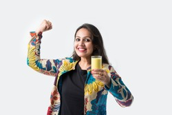 Pretty Asian Indian young woman holding or drinking turmeric milk in a glass -Healthy eating concept