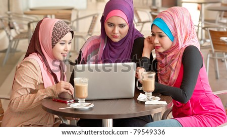 Pretty Asian Muslim college girls discussion while having lunch at coffee shop