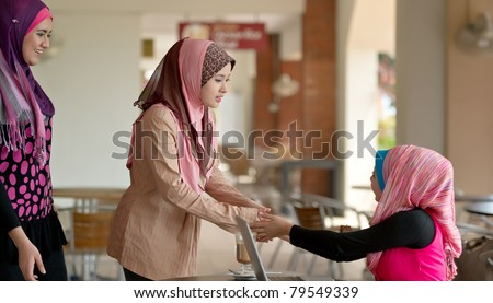 Pretty Asian Muslim college girls greeting friends at coffee shop