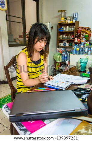 Pretty Asian Thai college girl university student in fashion vest is busy studying reading writing and doing homework on a messy desk with concentration.