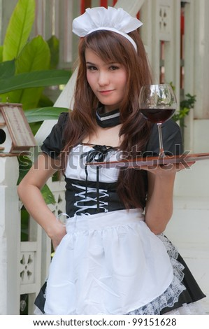 pretty asian waitress is holding wine glass in her hand for service - stock photo