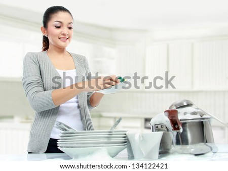 pretty asian woman doing house work, washing dishes