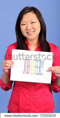 """Pretty Asian woman in bright red blouse holding a brightly colored """"Job Offer"""" sign and smiling against a blue background"""