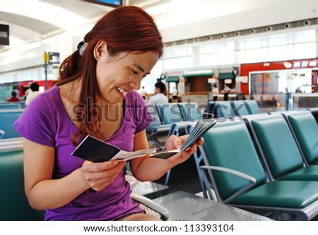 Pretty Asian Woman  in the Airport Checking her Passport and Boarding Pass