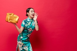 Pretty Asian woman in traditional costume holding gold gift box cupping hand and saying something in red isolated studio background for Chinese new year concepts