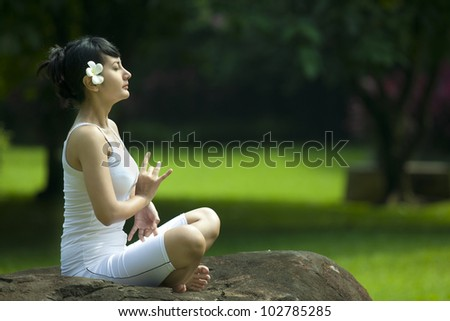 Pretty Asian woman in yoga position. Shot outdoor in a garden