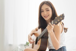 Pretty Asian woman is playing Acoustic guitar. Relaxing girl with the instrument in the white room at the house. copy space.