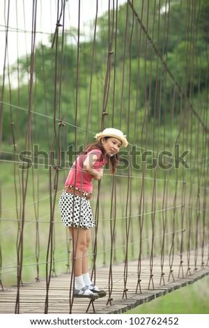 Pretty Asian woman standing at hanging bridge .