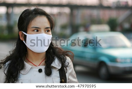 Pretty Asian woman wearing a face mask to protect against pollution or disease