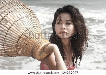 Pretty Asian woman with coop-like trap for catching fish in shallow water.