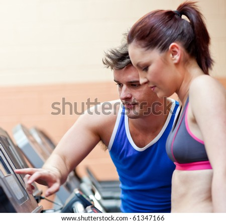 Pretty athletic woman standing on a running machine with her personal coach in a fitness center