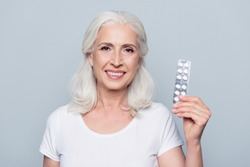 Pretty, attractive, nice, smiling woman present her favorite effective medical product from diseases, holding plate of tablets in hand, looking at camera over grey background