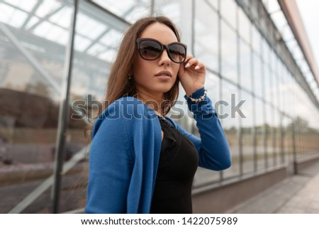 Pretty attractive young hipster woman with sexy lips in stylish sunglasses in a stylish blue knitted cape in a fashionable black lace top walks near a modern glass building. Beautiful girl model.