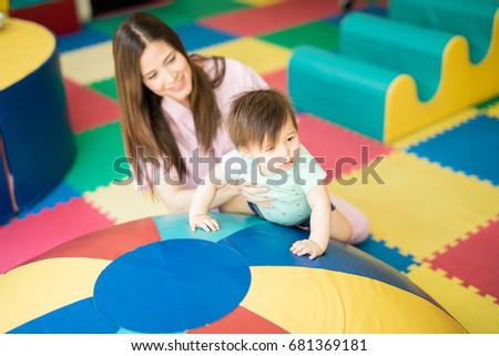 Pretty baby doing some early stimulation exercises and climbing a half sphere with the help of a therapist #681369181