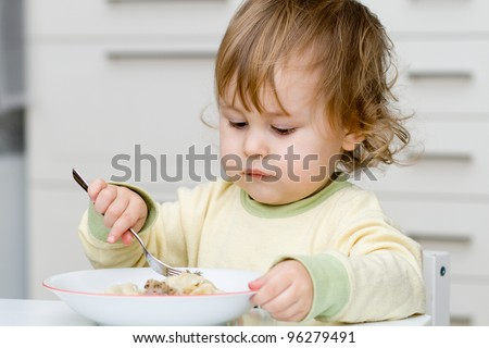 Pretty baby eating with plug
