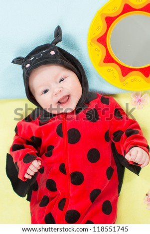 Pretty baby girl, dressed in ladybug costume on green background. The concept of childhood and holiday