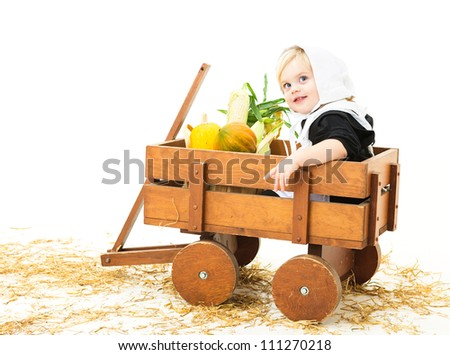 pretty baby girl dressed in pilgrim costume sitting in a wagon with her harvest produce
