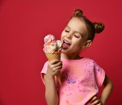 Pretty baby girl kid eating licking big ice cream in waffles cone with raspberry happy laughing on red background