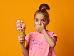 Pretty baby girl kid hold big banana and strawberry ice cream in waffles cone and close mouth with hand on yellow background