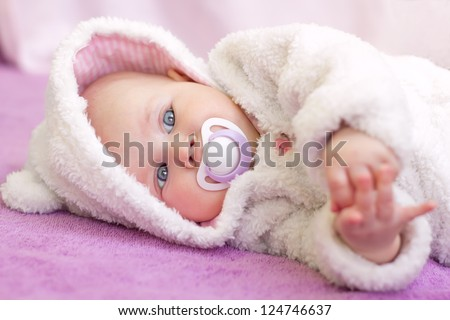 Pretty Baby Girl with big blue eyes in white fur with fluffy bear hood lying with nipple
