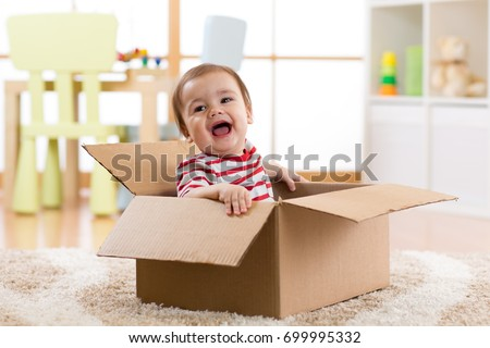 pretty baby infant boy sitting inside box in new house
