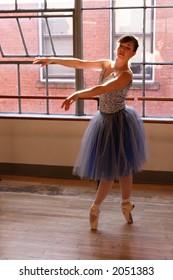 A stock photo of a pretty ballerina dancing in a studio.