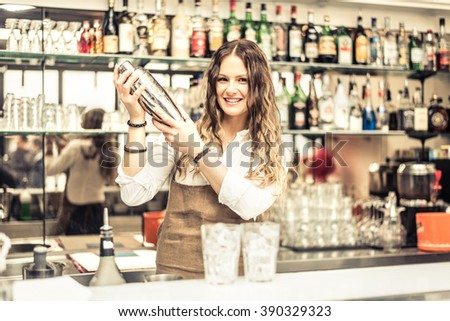 Pretty barmaid shaking cocktails in a bar - Female bartender preparing drinks for guests #390329323