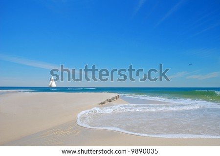 Pretty beach sand and dune with gentle waves with sailboat in distance under blue sky
