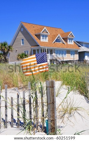 Pretty beach scene with rental home, dune and American flag. Perfect for cover art.