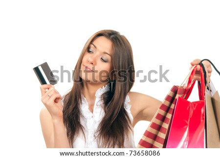 Pretty beautiful girl holding gift credit card in one hand and shopping bags presents in another on a white background.