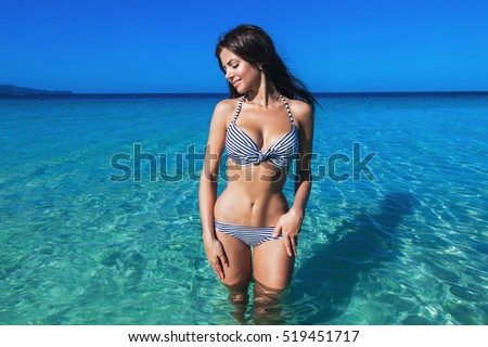Pretty beautiful woman in white swimwear bikini posing in blue sea water