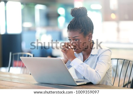 Pretty black female keeping hands clasped and looking at laptop screen while sitting at table, american student