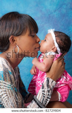 Pretty black mother holding her baby girl - stock photo