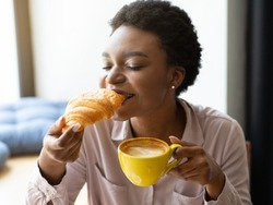 Pretty black woman enjoying relaxing atmosphere and tasty meal, having French croissant and coffee at cozy cafe. Young African American lady eating her breakfast with closed eyes, loving every bite