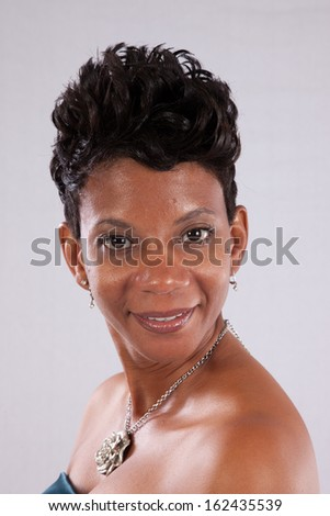 Pretty black woman  in a dress, her shoulders bare, and looking at the camera with a friendly, happy smile