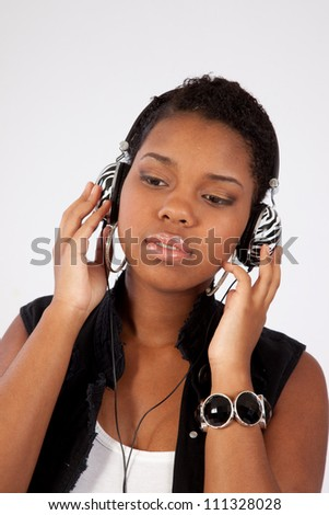 Pretty black woman listening to music with earphones around her neck and looking down with a pleased expression