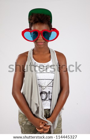 Pretty black woman playfully wearing heart shaped sunglasses in great fun