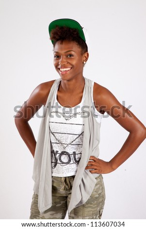 Pretty Black woman standing and looking at the camera with a big friendly smile with her hands on her hips