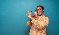 Pretty black woman with earpiece in her ears,holing phone and giving a quality gesture or assurance sign - concept on commercial products and services credibility