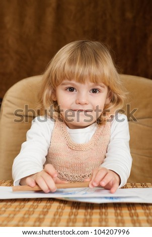 Pretty bliss young girl draws a table on a brown background