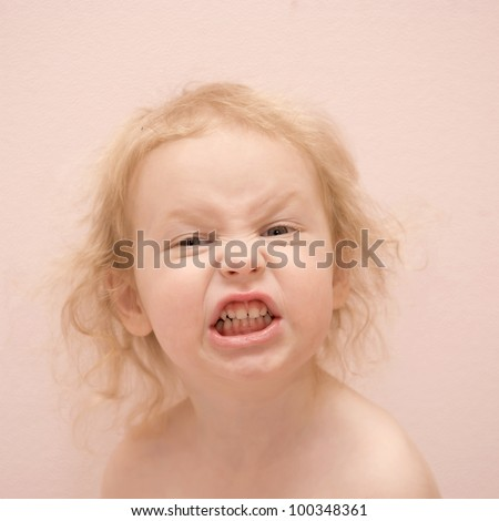 Pretty blond curly-haired baby girl with blue eyes grimace. Isolated on pink background - stock photo