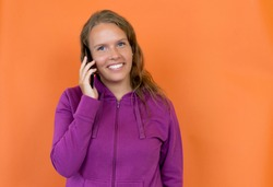 Pretty blond german young adult woman with hoody talking at mobile phone isolated on orange background