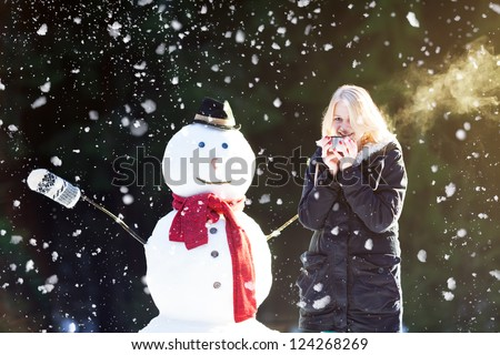 Pretty blond girl dinking tea outdoors with snowman while it's snowing