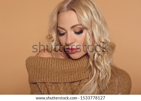 Pretty blond girl in knitted sweater over beige background. Blonde woman with short curly hairstyle posing isolated on studio. Fashion photo knit wear look style.