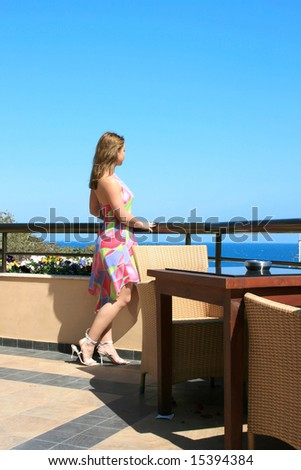 Pretty blond girl on the balcony watching the sea.