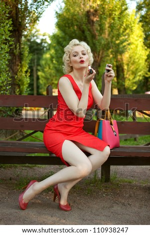 pretty blond pin up in red dress posing on a bench and applying make up. Woman looks like Marylin Monroe